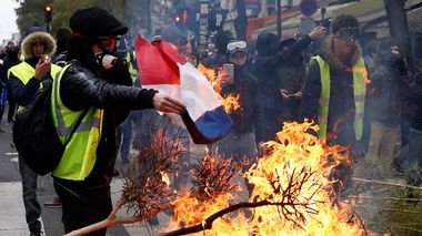 En demonstrant i gul vest brenner det franske flagget i Paris.                       (Foto: Reuters; Stephane Mahe)