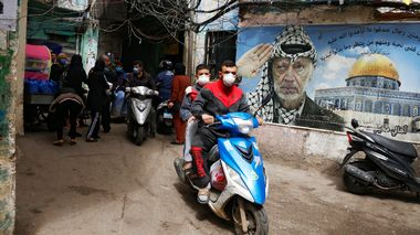 People on motorbikes wear face masks as they drive past a poster depicting late Palestinian leader Yasser Arafat in Shatila Palestinian refugee camp, as the spread of coronavirus disease (COVID-19) continues, in Beirut suburbs, Lebanon March 30, 2020. Picture taken March 30, 2020. REUTERS/Mohamed Azakir Bilder fra den palestinske flyktningleiren Shatila i Libanons hovedstad Beirut tatt 30. mars 2020.                       (Foto: MOHAMED AZAKIR MOHAMED AZAKIR, Reuters/NTB Scanpix)