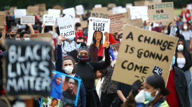 People wearing face masks hold banners in Hyde Park during a