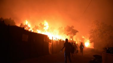 Refugees and migrants run as fire burns in the Moria refugee camp on the northeastern Aegean island of Lesbos, Greece, on Wednesday, Sept. 9, 2020. Fire Service officials say a large refugee camp on the Greek island of Lesbos has been partially evacuated despite a COVID-19 lockdown after fires broke out at multiple points around the site early Wednesday. (AP Photo/Panagiotis Balaskas) Migranter og flyktninger flykter fra brannene i Moria-leiren på Lesvos.                       (Foto: Panagiotis Balaskas Panagiotis Balaskas / AP / NTB scanpix)