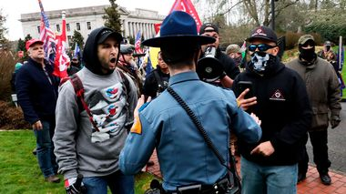 A Washington State Trooper tries to hold back supporters of President Donald Trump outside the Governor's Mansion after getting through a perimeter fence, Wednesday, Jan. 6, 2021, at the Capitol in Olympia, Wash., following a protest against the counting of electoral votes in Washington, DC, affirming President-elect Joe Biden's victory. The area was eventually cleared by police.  (Alan Berner/The Seattle Times via AP)                       (Foto: Alan Berner)