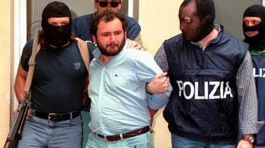 FILE - In this file photo taken on May 21, 1996, Giovanni Brusca is escorted by masked policemen outside Police H.Q. in Palermo, Sicily. Giovanni Brusca, 64, was released from prison this week after serving 25 years of a life term for some of Cosa Nostras most heinous crimes. They include the 1992 car bomb slaying of Italys leading anti-Mafia prosecutor and the 1996 kidnapping and murder of the 11-year-old son of a Mafia turncoat whose strangled body was dissolved in a vat of acid. Given the gravity of Bruscas crimes, his early release repulsed many Italians and prompted calls, especially from the right, to reform laws that allow for reduced sentences for mafiosi who break the mobster omerta, or wall of silence, and cooperate with investigators. (AP Photo/Alessandro Fucarini)                      (Foto: Alessandro Fucarini)