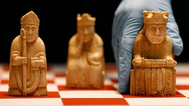 A worker at the British Museum arranges the Lewis Chessmen on a chess board in London March 16, 2009. The Lewis Chessmen, made of walrus ivory circa 1150-1200 AD, are among the museum's most popular objects and the most famous in the medieval collection and will form part of the exhibit in the museum's new medieval gallery. REUTERS/Andrew Winning (BRITAIN SOCIETY IMAGE OF THE DAY TOP PICTURE) Lewisbrikkene er utstilt på British Museum.                      (Foto: ANDREW WINNING Andrew Winning/NTB/SCANPIX)