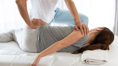 In bed, a woman is pelvic corrected by a man.                      (Foto: Shutterstock)