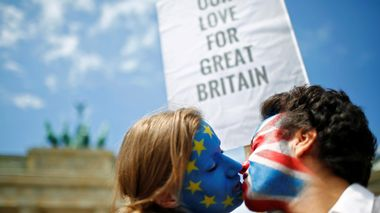 Two activists with the EU flag and Union Jack painted on their faces kiss each other in front of Brandenburg Gate to protest against British exit from the European Union, in Berlin, Germany, June 19, 2016. REUTERS/Hannibal Hanschke